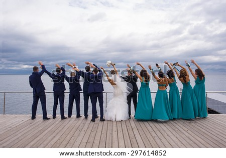 Guests on the wedding celebration are standing on the river quay, holding their hands up and playing the game. - stock photo