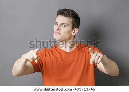 guilt concept - bossy young sporty man accusing or threatening someone with his hands for blame, grey background - stock photo