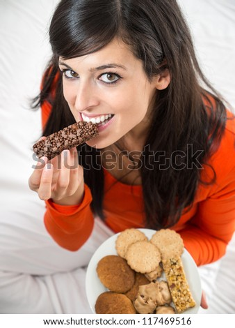 Guilty happy woman eating chocolate bar. Beautiful brunette woman tasting  delicious crunchy snack sitting on white bed indoor. - stock photo