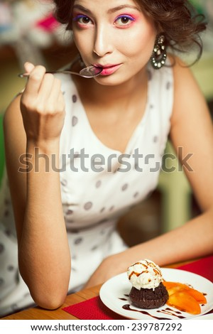 Guilty pleasure concept. Portrait of funny doll like brunette girl with retro hairdo in white trendy vintage polka-dot sleeveless dress eating cake in restaurant. Summer time. Close up. Indoor shot - stock photo