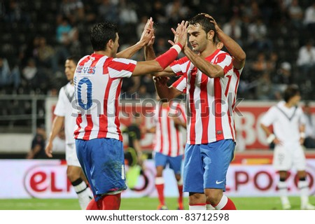 GUIMARAES, PORTUGAL - AUGUST 25: Adrian Lopes(R) from At.Madrid(ESP), celebrates with his teammates another goal at the 2011\2012 UEFA Europa League on August 25, 2011 in Guimaraes, Portugal - stock photo