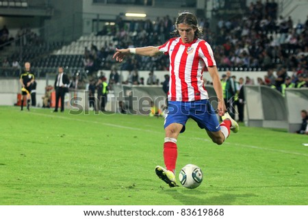GUIMARAES, PORTUGAL - AUGUST 25: Filipe Luis (R), from At.Madrid(ESP), tries to cross the ball at a 2011\2012 UEFA Europa League match on August 25, 2011 in Guimaraes, Portugal - stock photo