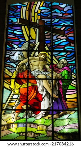 GUIMARAES, PORTUGAL - AUGUST 7, 2014: Stained glass window depicting Jesus taken from the cross in the Santos Passos church in Guimaraes, Portugal. - stock photo