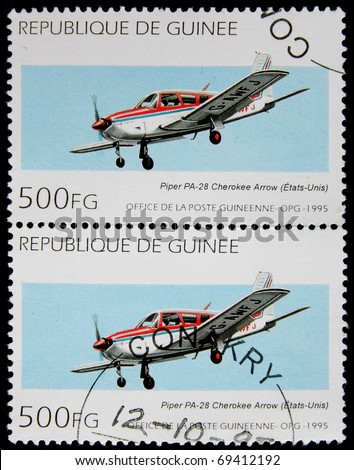 GUINEA  - CIRCA 1995: A post  stamp printed in Guinea  shows airplane PA-28 Cherokee Arow, Piper Aircraft. circa 1995