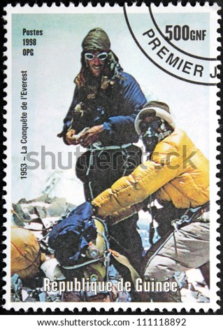 GUINEA - CIRCA 1998. A postage stamp printed by GUINEA shows Mont Everest first successful ascent by Edmund Hillary and Tenzing Norgay (1953), circa 1998. - stock photo