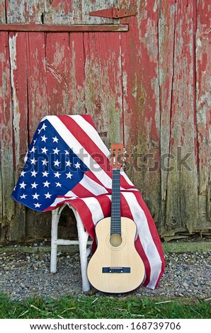 guitar and American flag by old red barn - stock photo