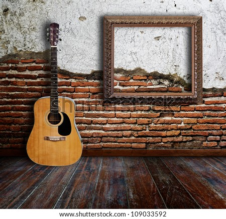 Guitar and picture frame in grunge room. - stock photo