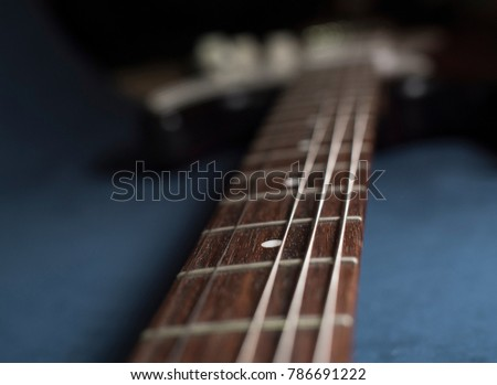guitar fretboard with shallow depth of field on dark blue velour