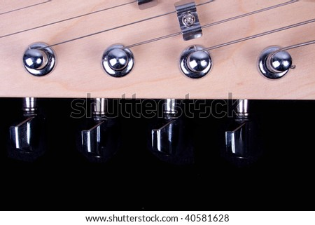 Guitar headstock, strings and tuners against a black background