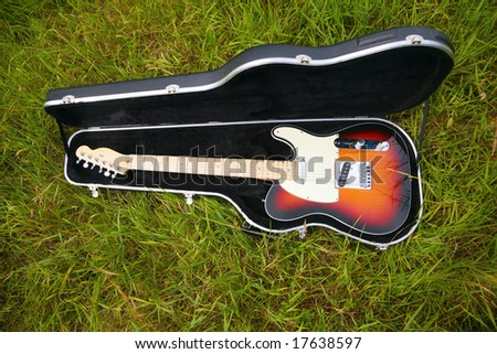 Guitar in case on grass - stock photo