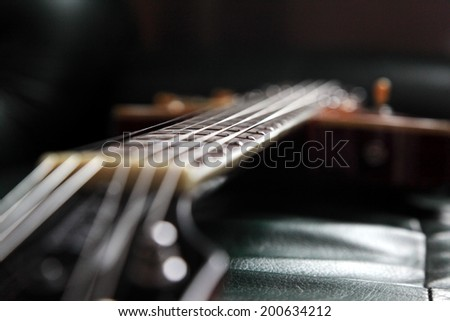Guitar in dark room, shallow depth of field. Natural lightning.  Note: image little bit softed - stock photo