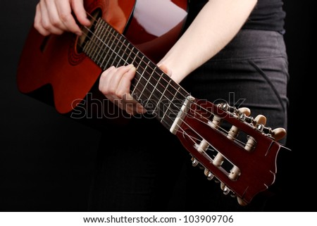 Guitar in hands isolated on black