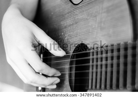 Guitar instrument. Musician or guitarist. Music, musical sound. Finger, hand on string. Acoustic concert closeup. Player play chord. Wood jazz, rock performance. Fretboard.