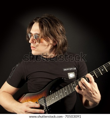 Guitar Man playing a guitar isolated on black background - stock photo