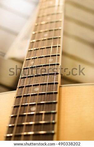 Guitar neck. Metal strings. Shallow depth of field