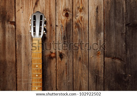 Guitar Neck on the old wooden wall - stock photo