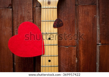 Guitar neck with red heart on wooden background - stock photo