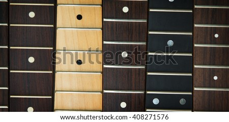 Guitar necks aligned, fretted rosewood, maple and ebony fingerboard necks with round dots for position marker.