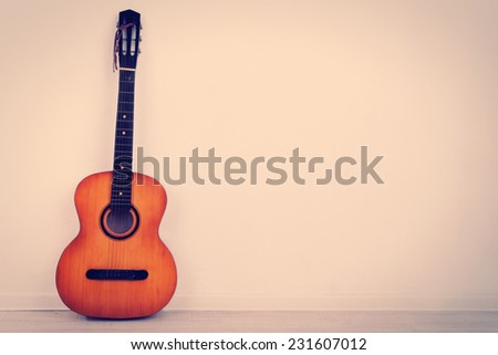 Guitar on the floor on wall background - stock photo