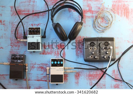 Guitar pedal, headset, audio card and guitar strings on grunge background - music concept - stock photo