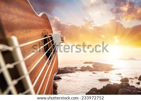 Guitar player at seascape sunset background  - stock photo