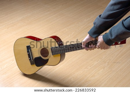 Guitar player attempting to destroy his instrument , over white
