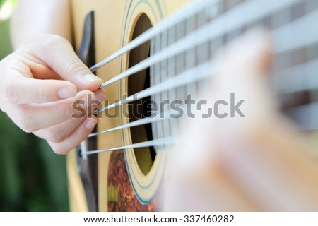 Guitar player,close up of 5 string acoustic bass guitar. - stock photo