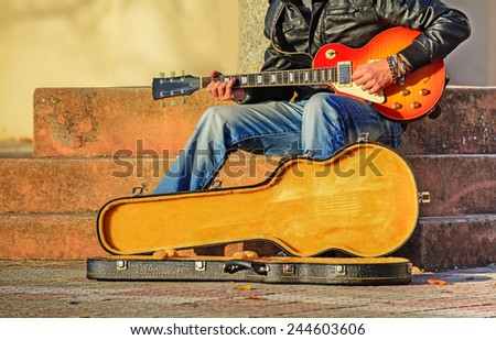 guitar player in the street with an open guitar case - stock photo