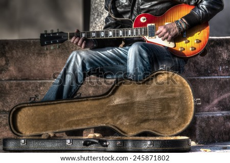 guitar player with an open guitar case in hdr - stock photo