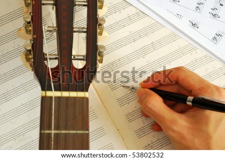 Guitar with hand composing music on manuscript. For concepts like music composition and creativity. - stock photo