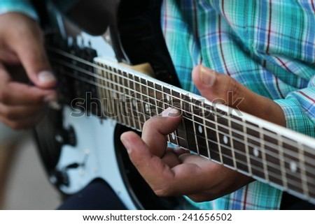 Guitarist hand play guitar on concert stage with blue light, Practicing in playing guitar. man playing guitar,rock and roll, electricity wood guitar background, song entertainment, music instrument - stock photo