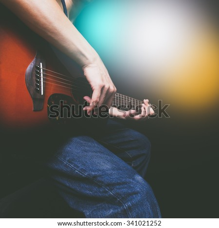 guitarist hands playing acoustic guitar on stage with colorful concert light - stock photo