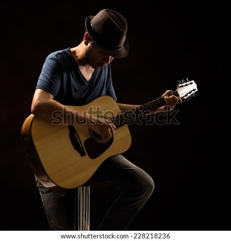 Guitarist in black hat playing guitar - stock photo