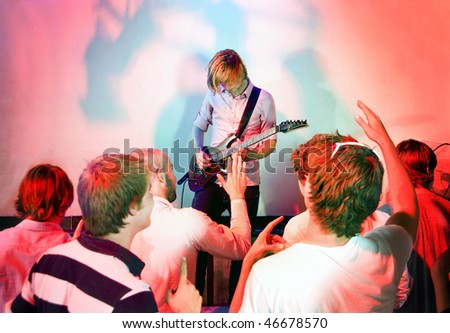 Guitarist, live on stage, in a club with a group of people watching the show - stock photo