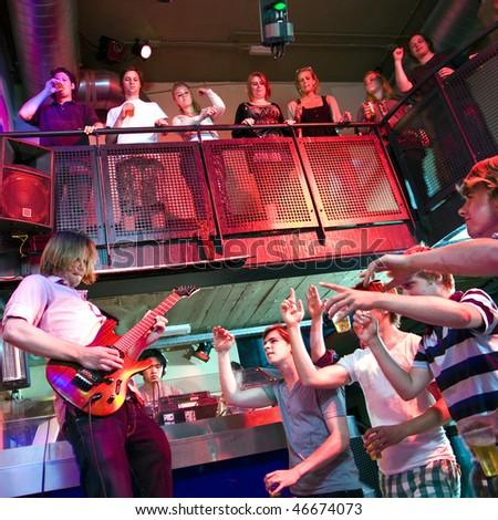 Guitarist, performing live in a nightclub accompanied by a DJ, performing in a nightclub - stock photo