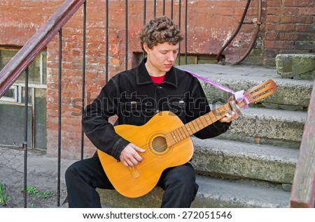 Guitarist playing his guitar of classical musical instrument on the street - stock photo