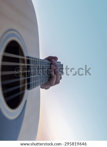 Guitarist Playing on the Acoustic Guitar at purple Sunset at lake - stock photo