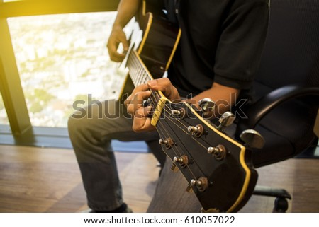 Guitarist plays guitar on wooden background, close up.