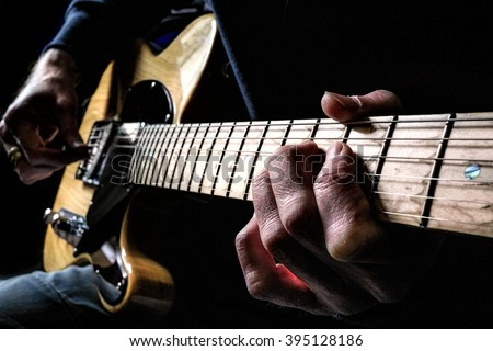 Guitarist strumming a guitar late at night in a dark room writing songs. - stock photo