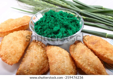 gujia, indian traditional snacks for holi festival with green color in bowl - stock photo