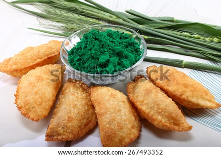 gujia, indian traditional snacks for holi festival with green color in bowl