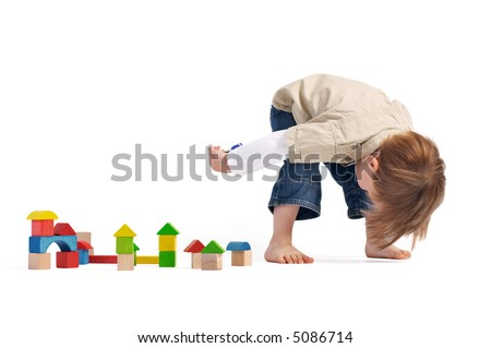 Gulliver in the Country of Lilliputs. Cute 3-years old boy and small town build from wooden blocks.