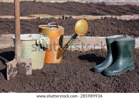 Gumboots, shovel, watering can, bucket against a fresh bed - stock photo