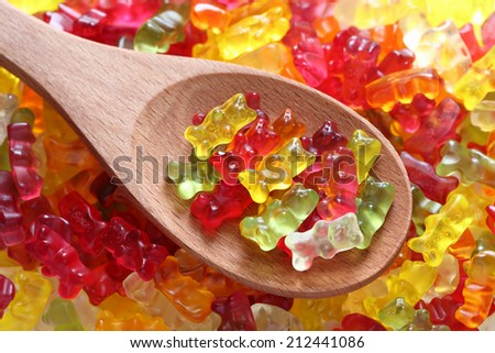 Gummy bears on a wooden spoon on a gummy bear background. Close-up. - stock photo