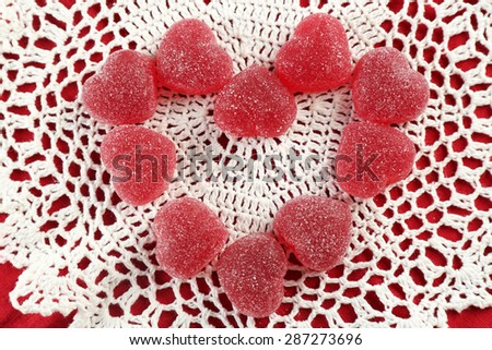 Gummy candies arranged in heart shape on fabric background - stock photo