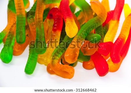 Gummy candies in the shape of a snake on a white background. - stock photo