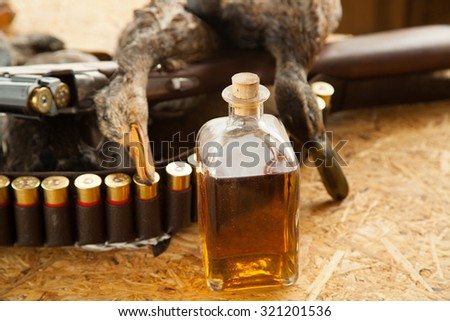 Gun, a bottle of brandy, hunting ammunition on the table