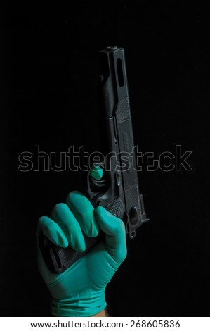 Gun and a Hand on a Black Background - stock photo
