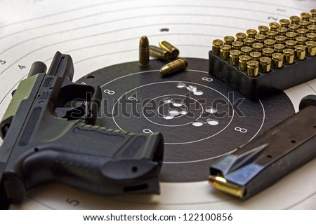 gun and ammunition over bulls eye score - stock photo
