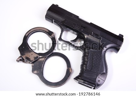 Gun and handcuffs isolated on white background - stock photo